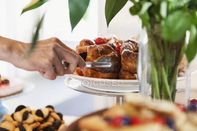 Imagem cortada da mão que arranja o deserto no cakestand no café — Fotografia de Stock