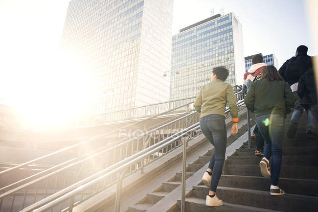 Low angle view of friends walking up on steps by buildings in city — Stock Photo