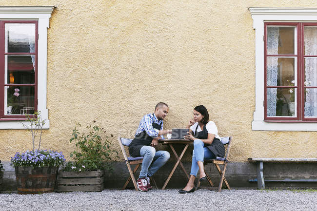 Bakers discussing over digital tablet while sitting at table outside cafe — Stockfoto