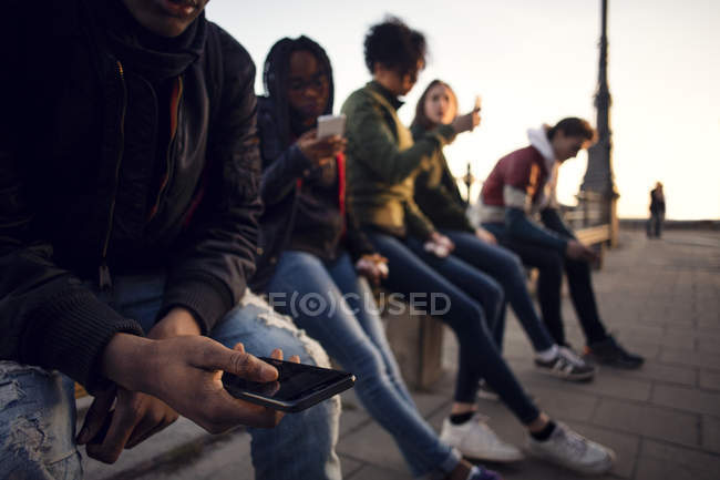 Friends using phone while sitting on railing at city square — Stock Photo