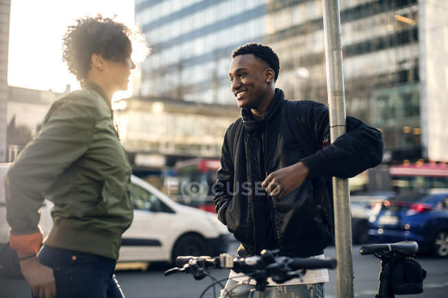 Smiling friends standing against cars on street in city — Stockfoto
