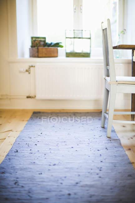 Стул и ковер на деревянных полах дома — стоковое фото