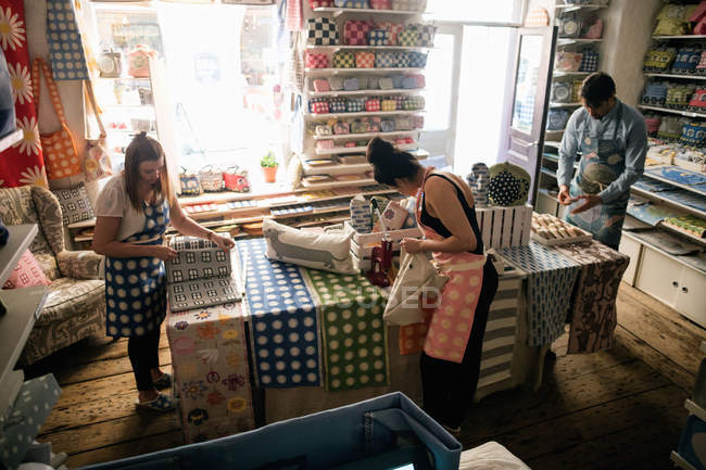 High angle view of owners working in fabric shop — Stockfoto
