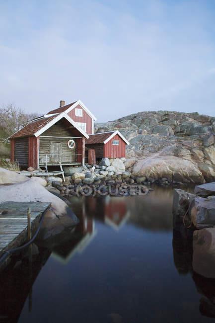 Boathouse на скелястому березі проти чистого неба — стокове фото