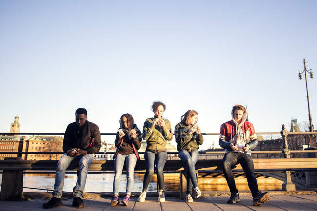 Full length of teenage friends sitting on railing while having snacks against clear sky — Stock Photo