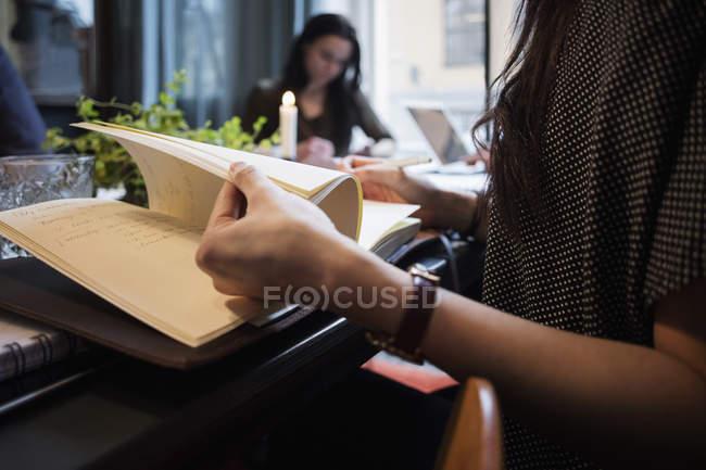 Sezione centrale della donna voltando le pagine seduto a tavola in ufficio creativo — Foto stock