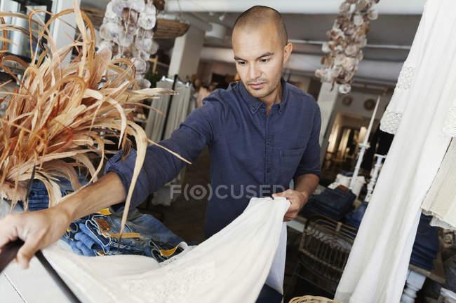 Owner checking white dress at fashion store — Stockfoto