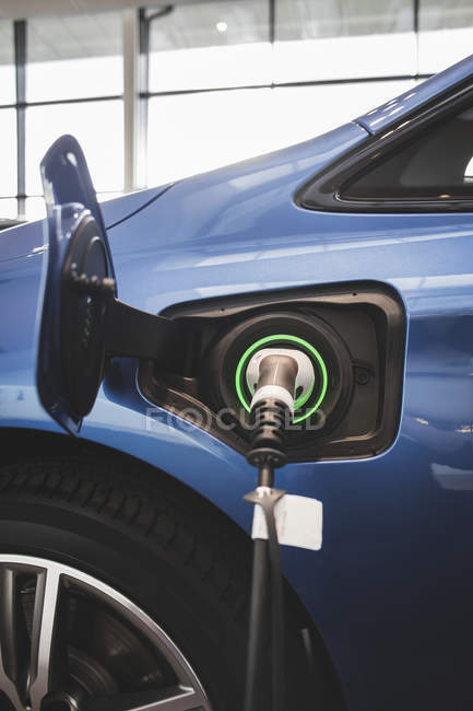 Battery charger in blue electric car at showroom — Stock Photo