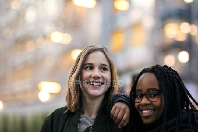 Portrait of teenage girl with smiling friend at dusk — Stockfoto