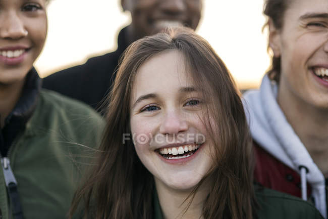 Portrait of teenage girl standing with friends — Stockfoto