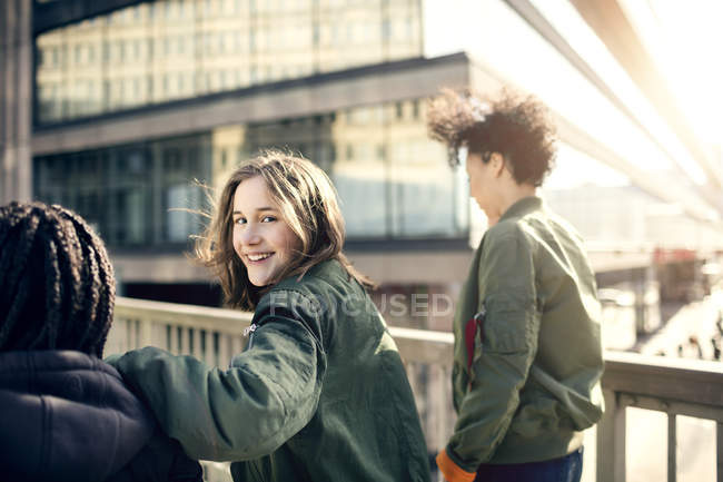 Portrait of smiling teenage girl walking with friends on bridge in city — Stock Photo