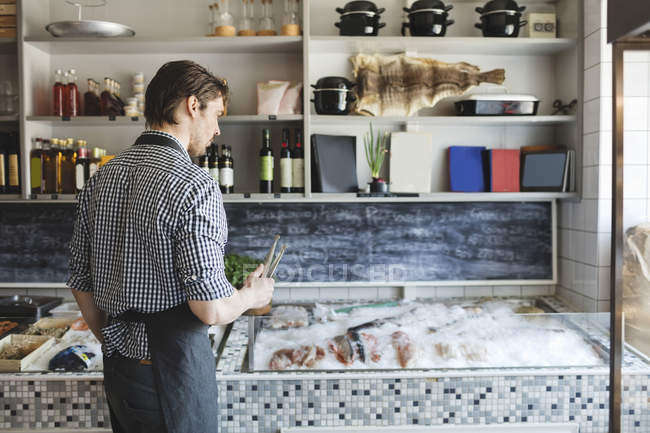 Male owner standing by retail display at fish store — Stock Photo