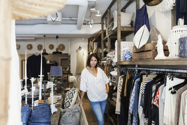 Портрет уверенной владелицы, стоящей у стойки с одеждой в магазине — стоковое фото