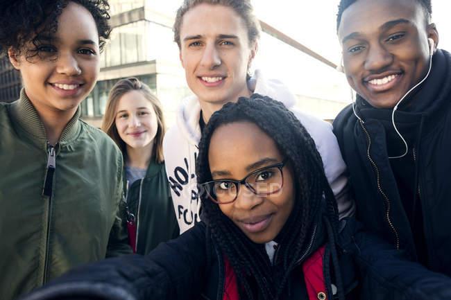 Portrait of smiling teenage friends in city — Stockfoto
