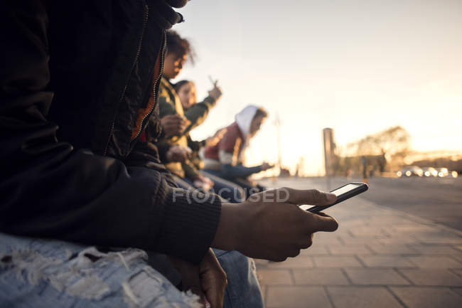 Midsection of teenager using phone while sitting with friends by cobbled street — Stock Photo