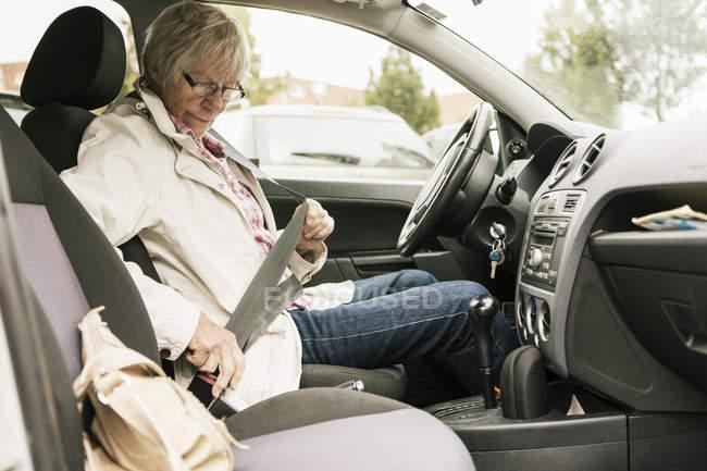 Seniorin schnallt Sicherheitsgurt im Auto an — Stockfoto