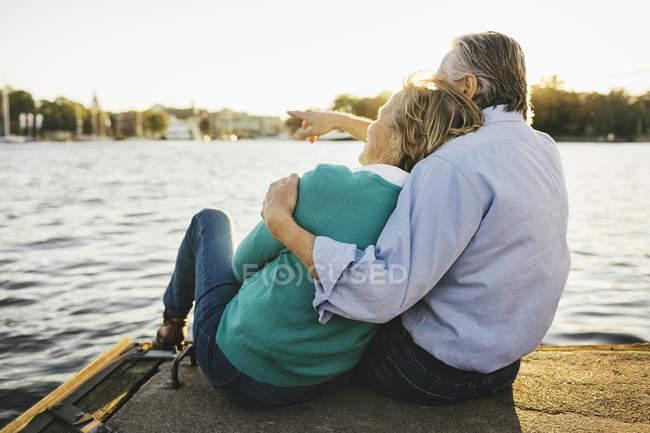 Homem sênior que mostra algo à mulher ao sentar-se no cais — Fotografia de Stock