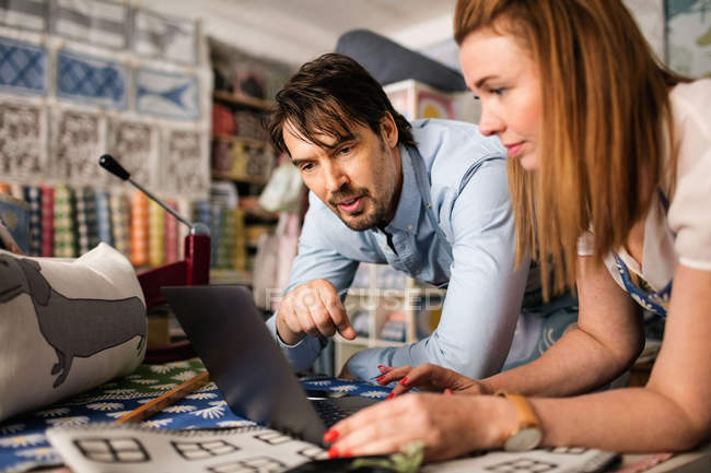 Male and female owners using laptop in fabric shop — Stockfoto
