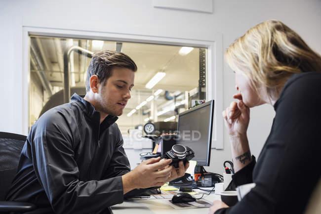 Propietario masculino que muestra pieza de repuesto a las mujeres en el despacho - foto de stock