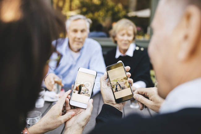 Senior couple looking at photos on mobile phones at outdoor restaurant — Stock Photo