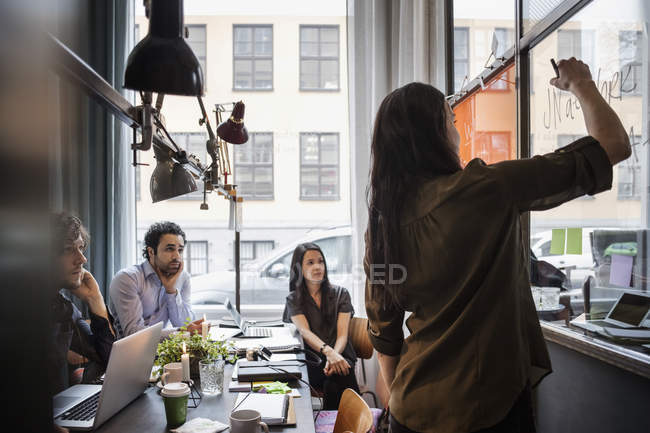 Creative business people looking at female coworker writing on glass in office — Stock Photo