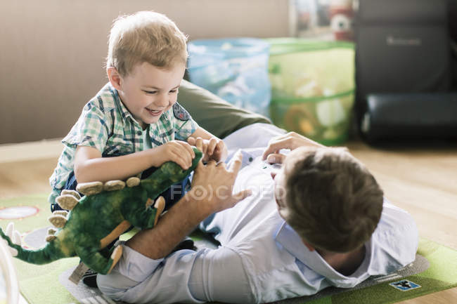 Father and son playing with stuffed toy at home — Stock Photo