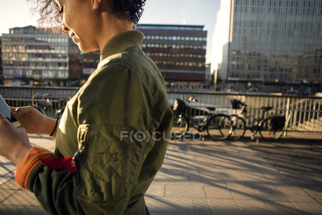 Midsection of teenage girl using phone by street and buildings in city — Stock Photo