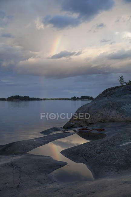 Мальовничий вид на озеро з скелястий берег проти хмарного неба — стокове фото