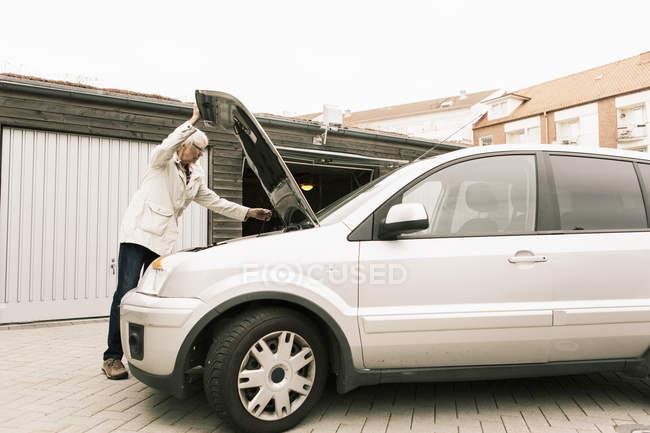 Старша жінка відкриття автомобіля капот стоячи на складі — стокове фото