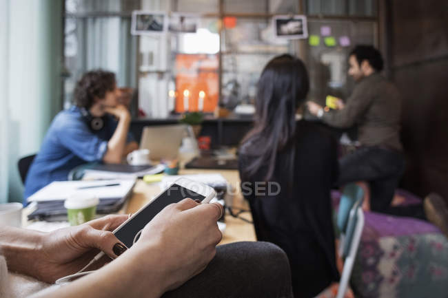 Close-up of woman holding mobile phone against colleagues working in creative office — Stock Photo