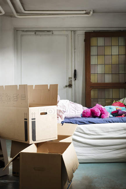 Cajas de cartón en el dormitorio de la casa nueva - foto de stock