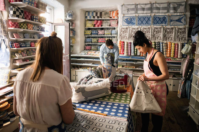 Male and female owners working in fabric shop — Stockfoto