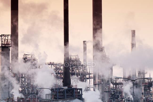 Fumo dalle tubature in fabbrica contro il cielo al tramonto — Foto stock