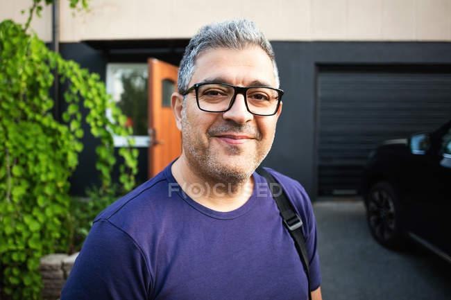Uomo sorridente che indossa occhiali in piedi contro casa — Foto stock