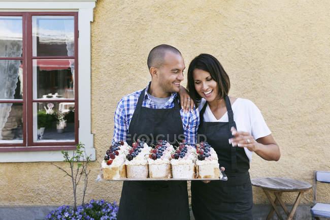 Padeiros de sorriso que prendem a bandeja de pastelarias ao estar de encontro à parede fora do café — Fotografia de Stock