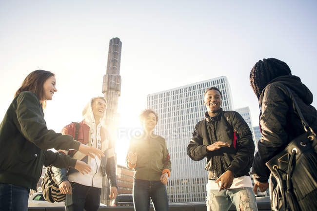 Low angle view of happy teenagers dancing in city against clear sky — Stock Photo