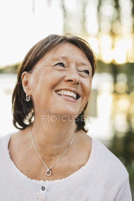 Thoughtful senior woman looking up and smiling outdoors — Stock Photo