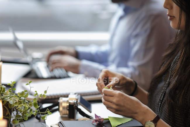 Imagen recortada de la mujer haciendo origami mientras está sentada de compañero de trabajo en la oficina creativa - foto de stock