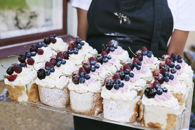 Bandeja fêmea da terra arrendada do padeiro das pastelarias fora do café — Fotografia de Stock