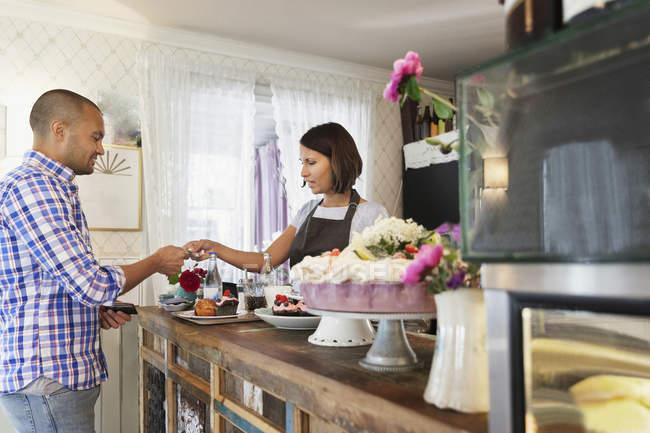 Клиент, дающий кредитную карту женщине-хозяйке в кафе — стоковое фото