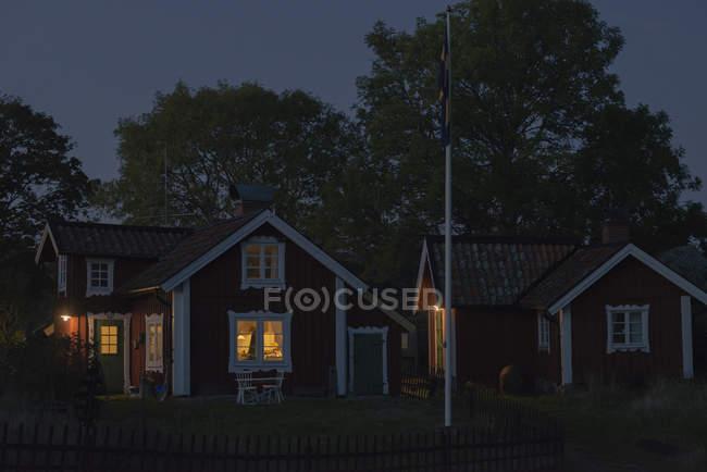 Beleuchtete Holzhäuser auf Feld in der Abenddämmerung — Stockfoto