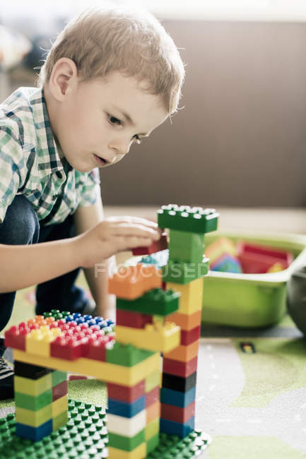 Boy playing with toy blocks at home — Stock Photo