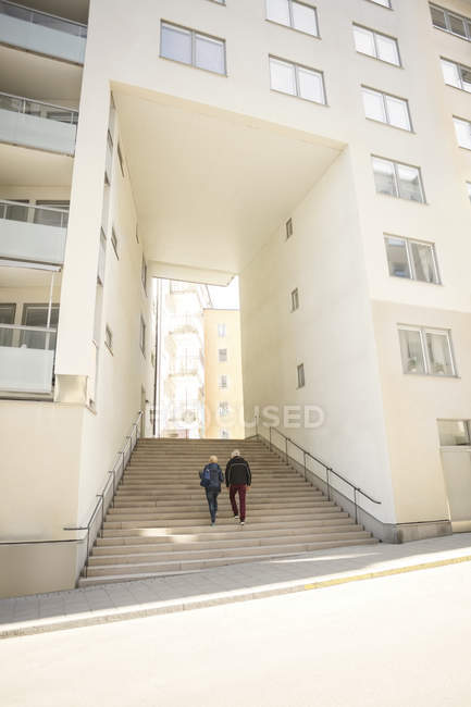 Couple walking on steps leading towards entrance of building — Stock Photo