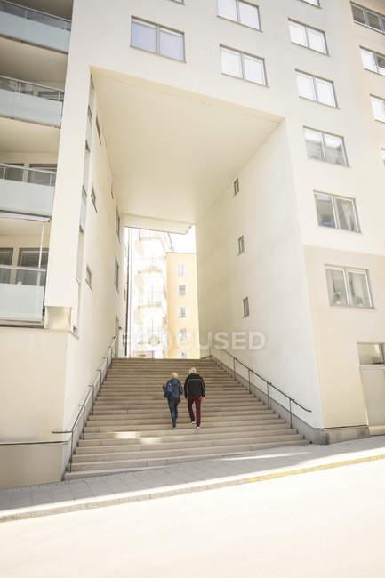 Casal caminhando em degraus que levam à entrada do edifício — Fotografia de Stock