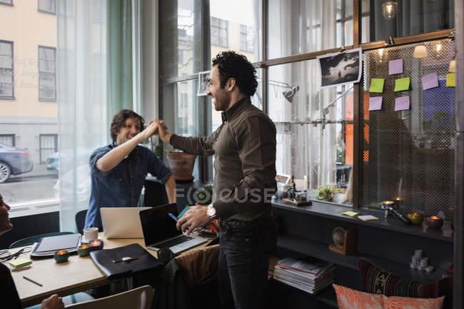 Heureux hommes d'affaires high-fiving dans le bureau de création — Photo de stock