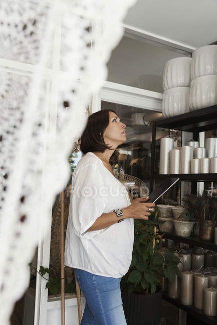 Female owner using digital tablet while analyzing objects at store — Stock Photo