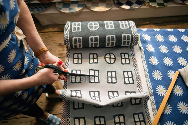 Midsection of woman cutting fabric swatch in shop — Stockfoto