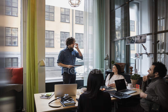 Creative businessman sharing ideas with team in modern office — Stock Photo