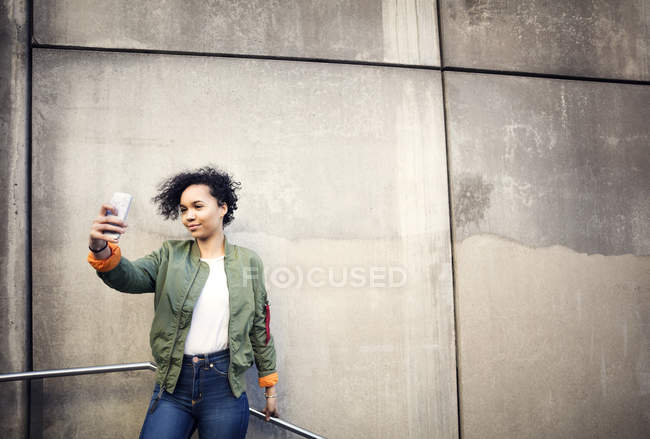 Smiling teenage girl taking selfie while standing against weathered wall — Stock Photo