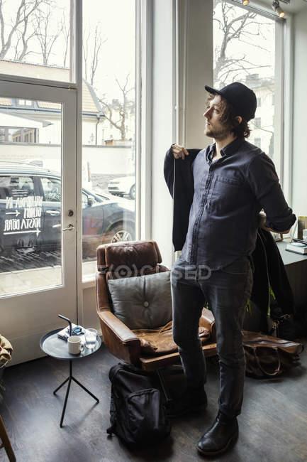 Повна довжина бізнесмена носіння куртки, стоячи в творчому кабінеті — стокове фото